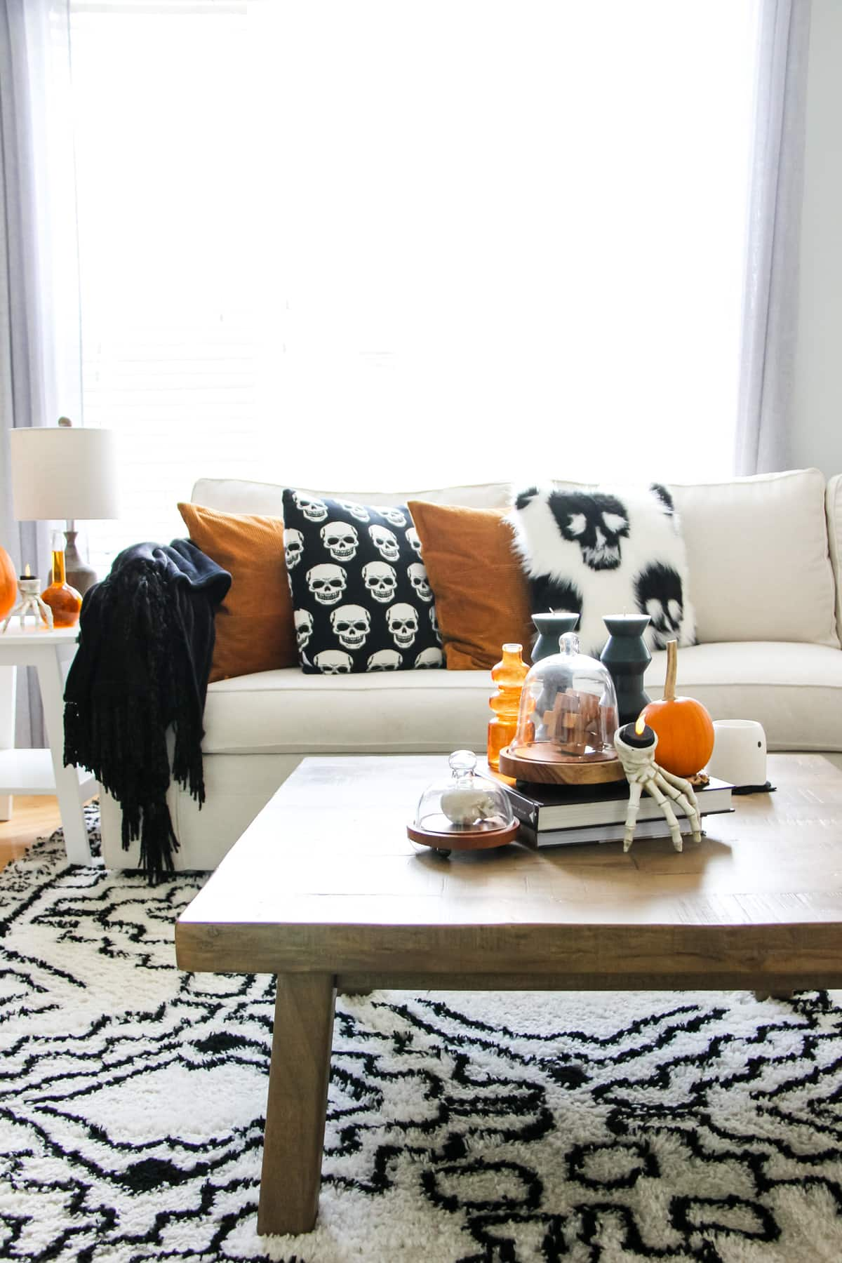 a cream coloured couch with black and white skull pillows and burnt orange pillows. in the forefront is a wooden coffee table filled with Halloween decorations
