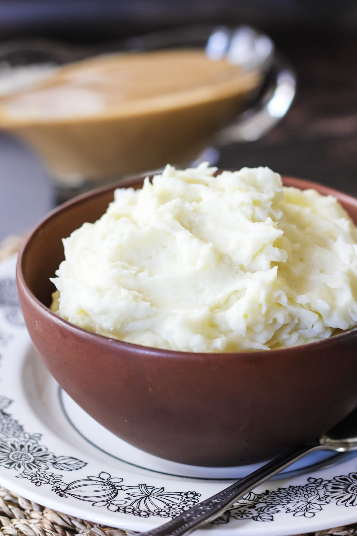 a brown bowl filled with creamy Mashed Potatoes. in the background is a gravy boat filled with gravy