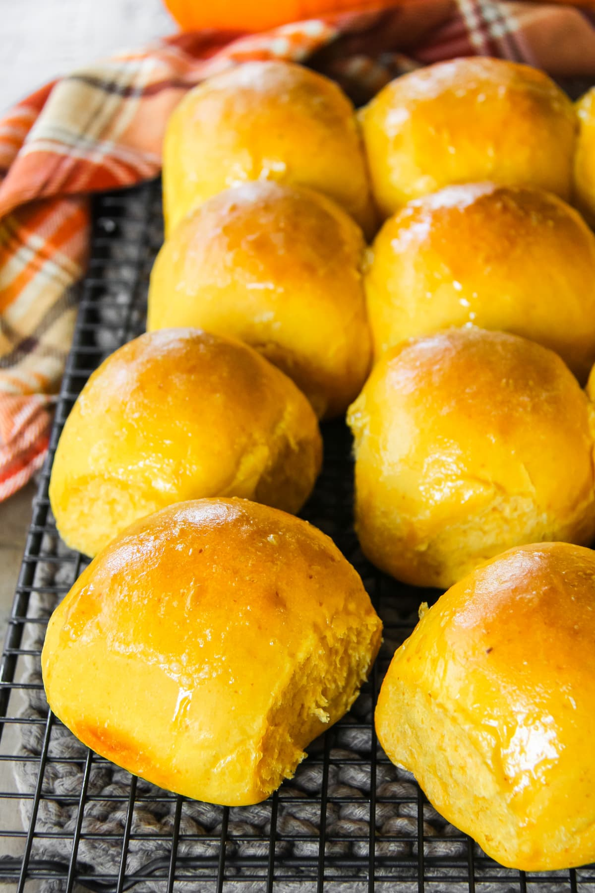 freshly baked Pumpkin Dinner Rolls cooling on a black wire cooling rack. off to the side is an orange plaid napkin