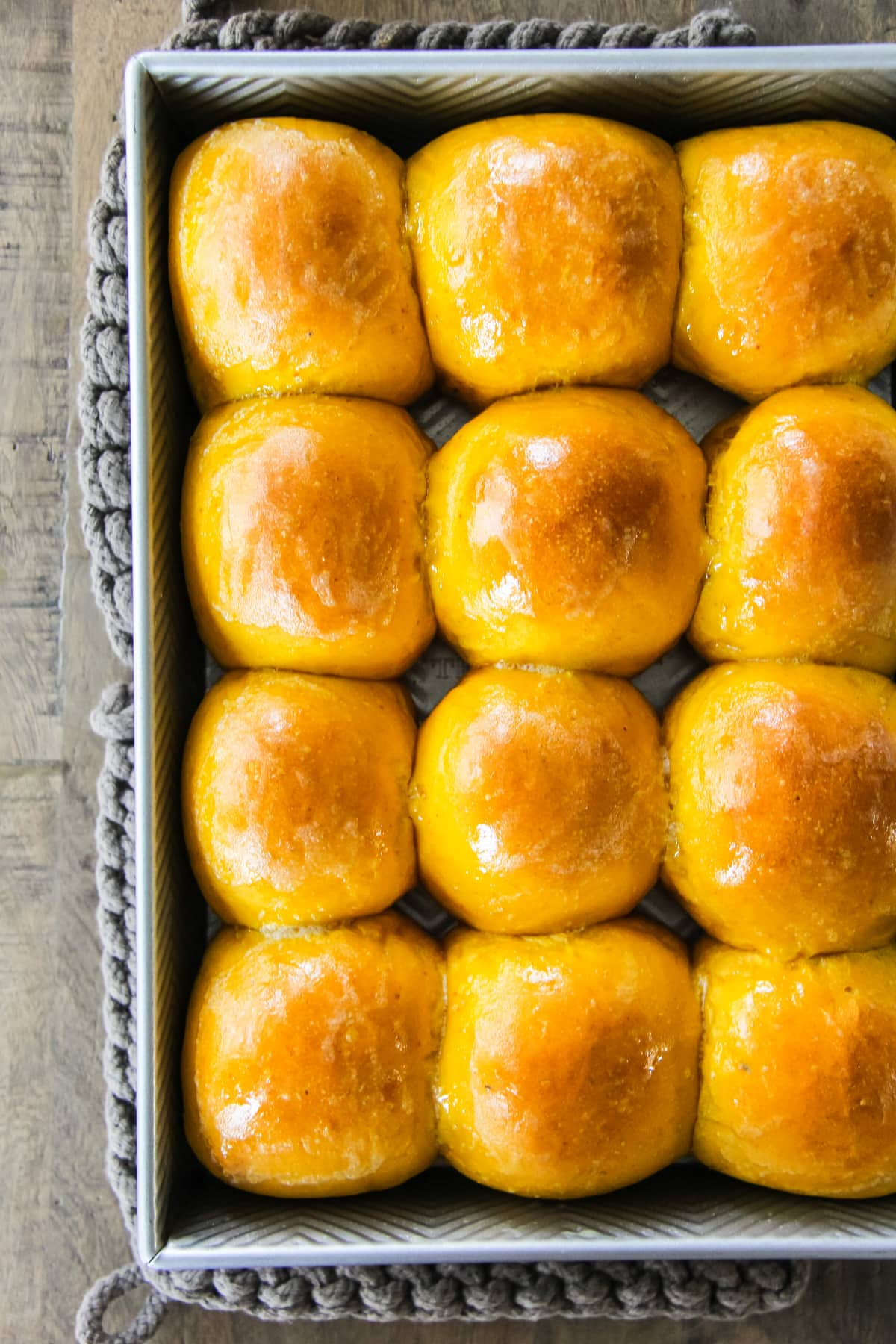 a top down view of a metal baking pan filled with freshly baked Pumpkin Dinner Rolls.